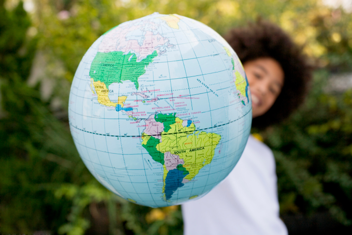 Boy holding globe, representing larger world full of dozens of religions