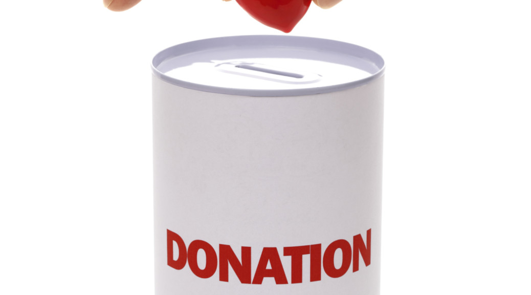 A can labeled donation with a heart being dropped in