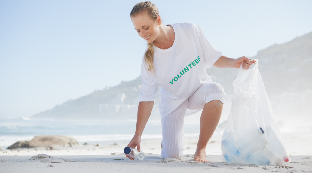 Woman cleaning up trash left on the beach