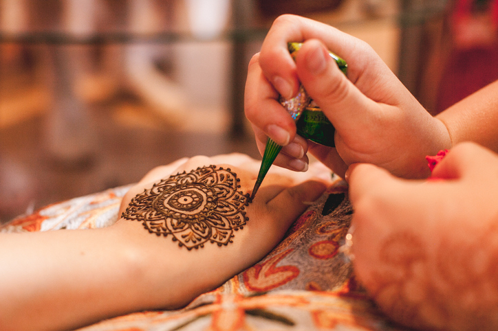 Intricate henna body art is applied to the bride in a prenuptial ceremony with her closest female friends.